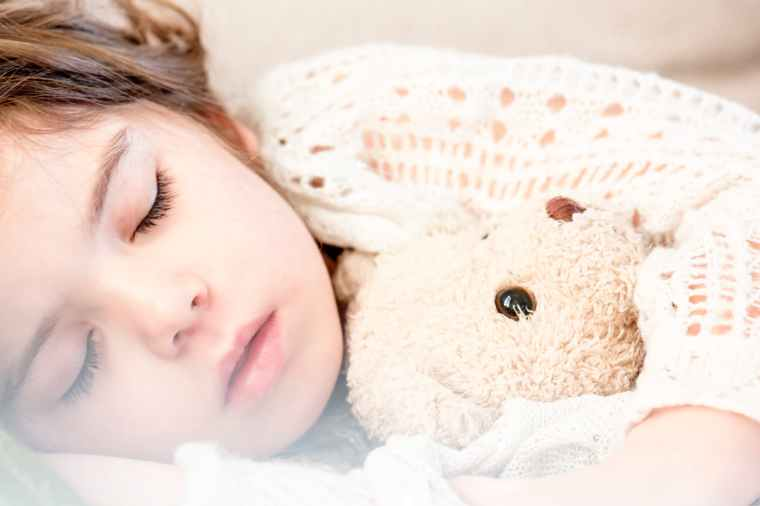 Image of a sleeping toddler with a soft bear
